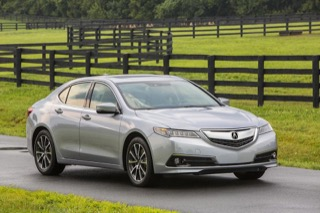 An Acura TLX ion front of a long, winding fence.