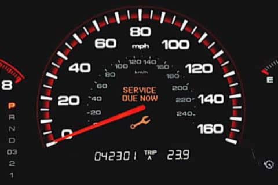 A gauge cluster with an orange wrench warning light labeled 'Service Due Now'