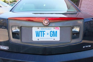 The back of a CTS with the license plate spelling WTF GM