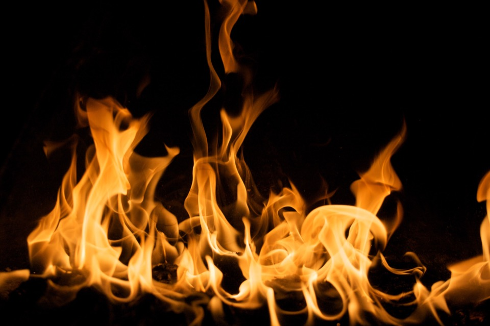 An orange and yellow flame on a black background