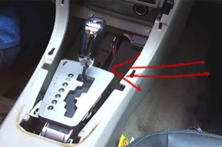 Red arrow points at a disassembled gear shifter