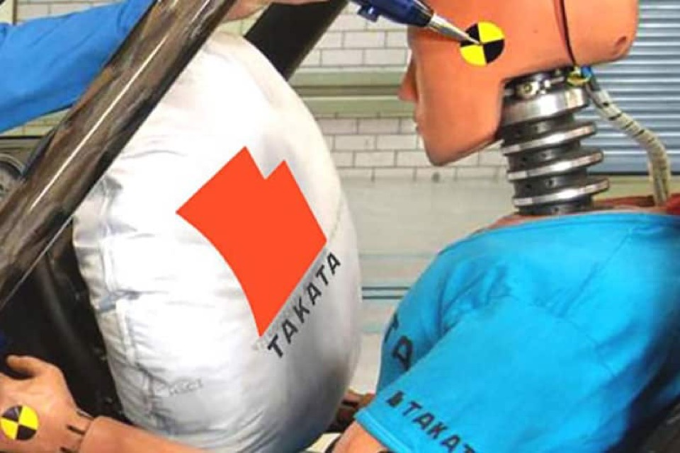 A crash test dummy about to hit an airbag superimposed with the Takata logo