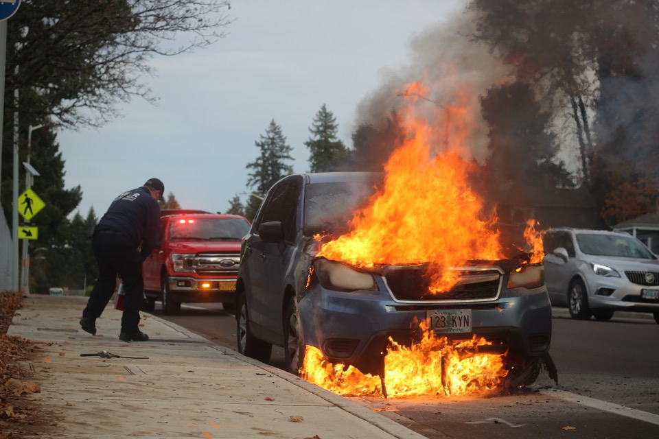 Emergency workers near a car with its engine on fire