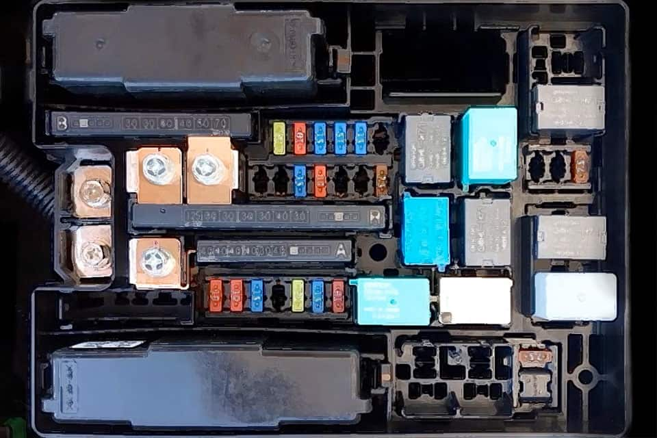 An overhead view of a car's fuse box with various colored fuses