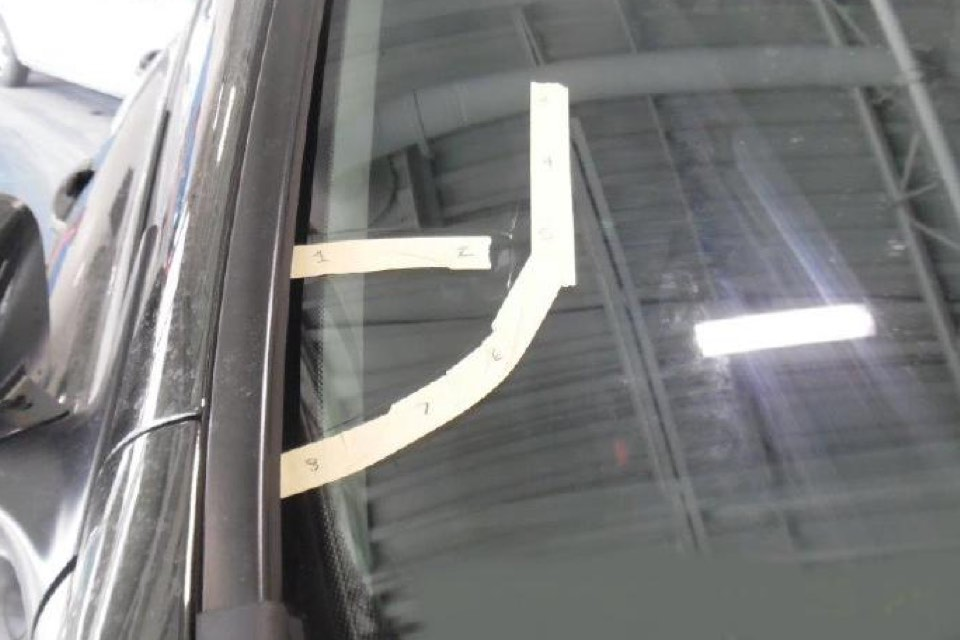 A windshield with cracks in the lower left corner covered in tape