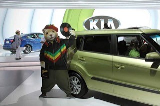 A hamster holding a record in front of a green Kia Soul, from an advertising campaign.