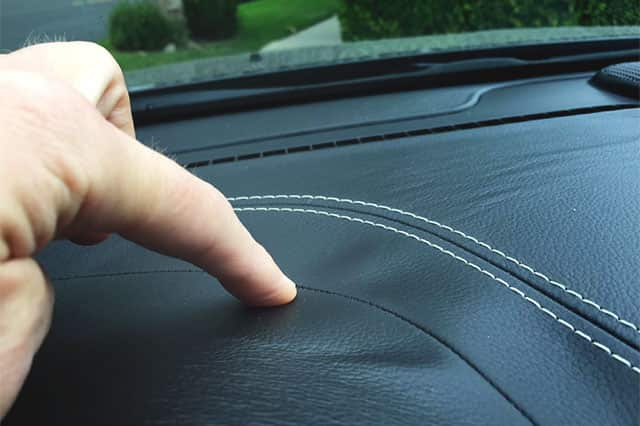 A finger pointing to the wrinkles in a black dashboard