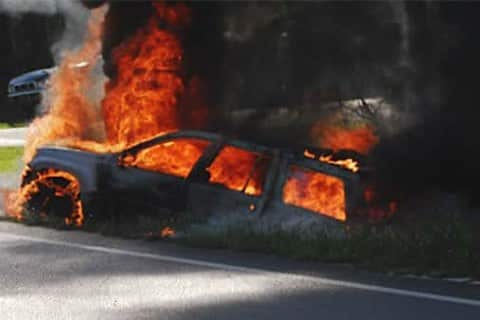 A Jeep on fire on the side of the road