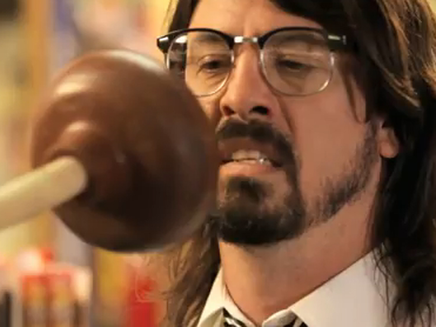 Dave Grohl making a yucky facial expression as a plunger gets closer to his face