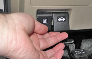 A hand opening a black hood release switch, which is right next to the fuel door switch