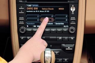 A hand pressing the touchscreen interface of Porsche's PCM infotainment system