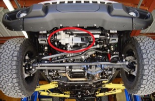 A red circle highlights the sway bar disconnect system on the bottom front of a Ram hoisted up on lifts.