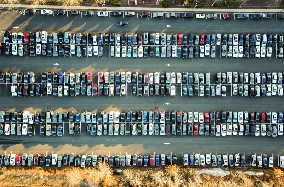 An overhead view of a parking lot with cars neatly lined up inside parking spaces.