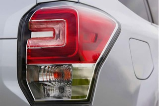 Close-up of a brake light with a red lens on top, clear lens on bottom.