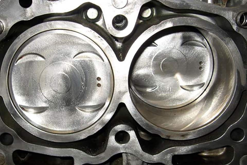 A close-up of a clean black head gasket above two silver pistons.