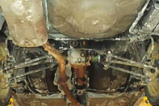 The underside of an abundantly rusted Subaru up on a car lift.