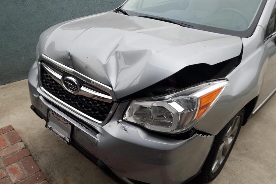 Smashed front hood of a gray Subaru
