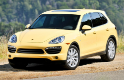 A yellow Porsche Cayenne Hybrid on the side of the road with evergreen trees in the background
