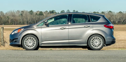 Side view of a gray C-Max Hybrid in front of a field on a sunny day