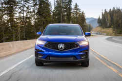 Bright blue Acura SUV on a mountain road