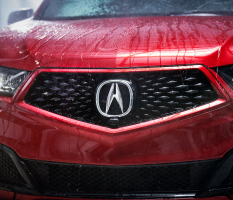 A red Acura's grille, logo prominently displayed, after a car wash