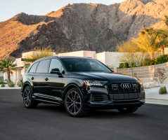 A black Q7 parked on a street with glowing mountains in the background.