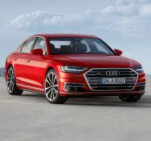 Front three-quarters of a red Audi with a cloudy sky in the background