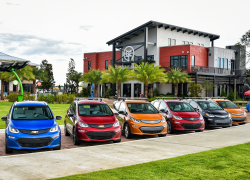 A line of colorful Bolt EVs all parked in front of a civic building