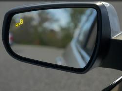 Yellow blind spot warning icon appears on a sideview mirror