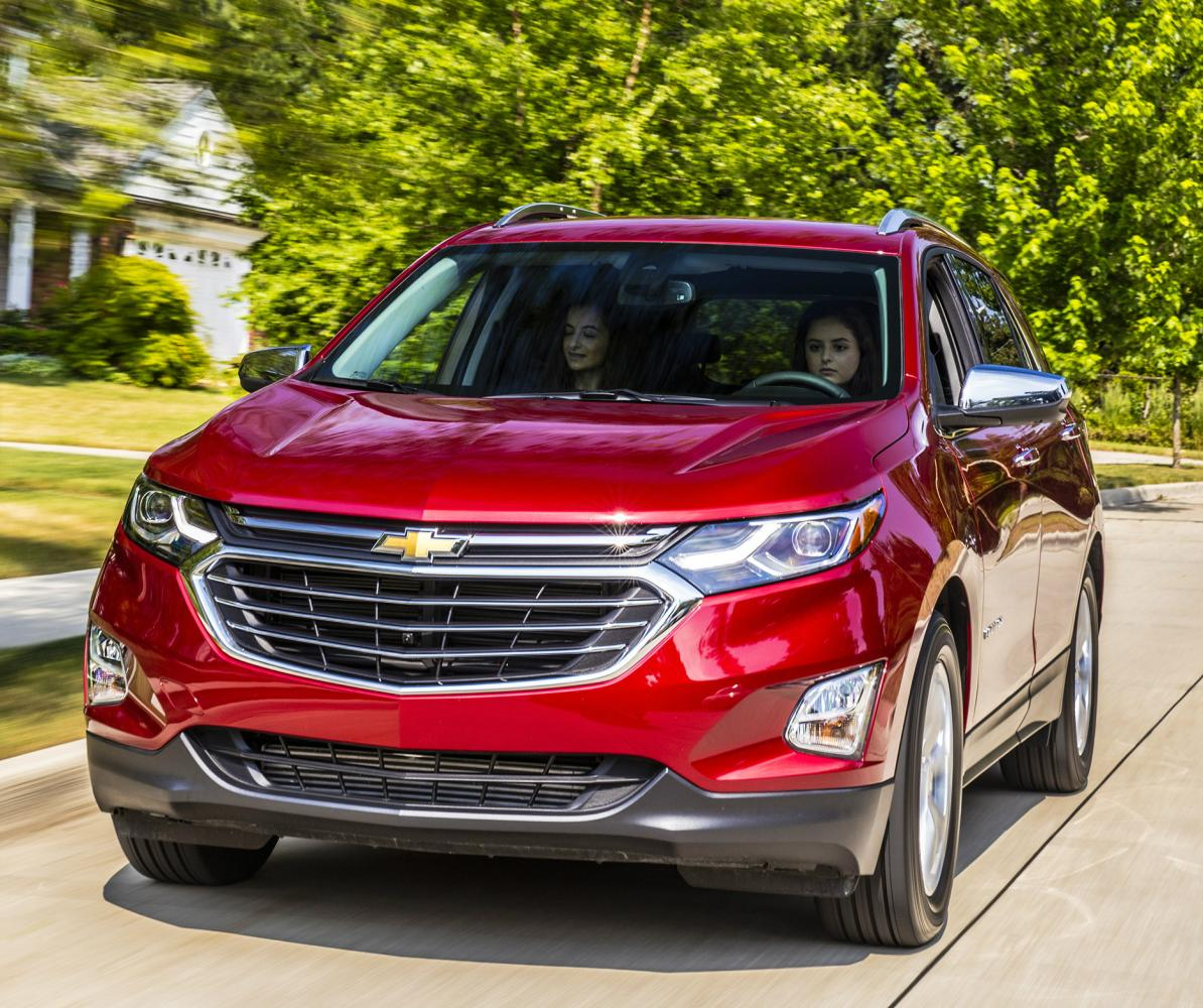 Two young woman driving a red Chevy Equinox with blurred green trees in the background