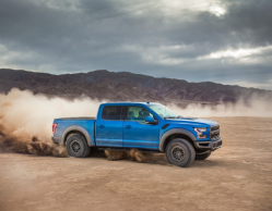 A blue F-150 is riding through a flat, sandy area with a plume of dust behind it