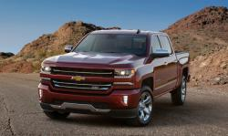 A red Silverado truck in front of mounds of dirt