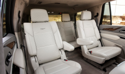 Looking back towards the second and third row seats of a GM SUV with white interior.