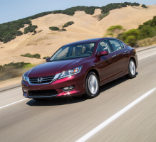 A maroon Accord driving down the road with hills in the background