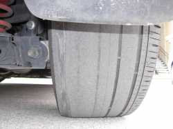 Tread pattern of a Civic tire shows significant wear on the inside of the tire. The tire is nearly bald on one side.