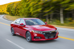 A red sedan on a windy road surrounded by blurred trees