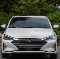Front view of a white Hyundai parked in front of some greenery