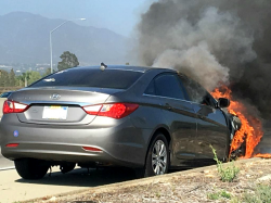 Hyundai sedan on the side of the road with the engine compartment in flames and thick smoke.
