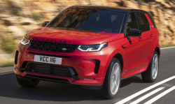 A red Discovery Sport drives down the road