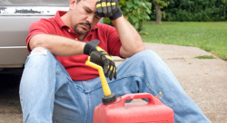 A frustrated man sits on the ground in front of a red gas can