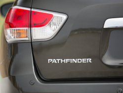 The red lens of a brake light above the Pathfinder emblem on the trunk