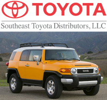 A bright orange FJ Cruiser displayed under the Southeast Toyota Distributors logo