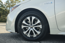 The front left wheel of a white Prius