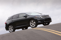 A black Venza at the top of a hill on a paved road.